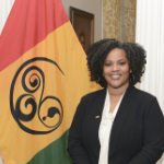 A Black woman stands beside a flag with red, yellow, and green vertical bands, with a black curlicue design in the center of the yellow area