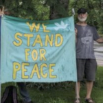 """A man holds a sign reading """"We stand for Peace""""."""