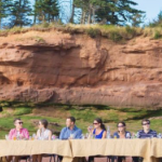 Six rich white people sit on the same side of a long table on the ocean floor, eating and drinking fine food and wines.