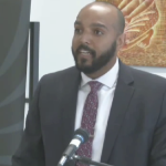 Brandon Rolle, a Black man, speaks into a microphone at a podium.