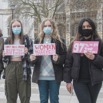 Three women hold signs protesting street harassment.