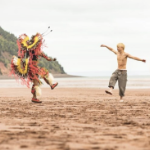 A person in Indigenous ceremonial dress and a boy dance on a red sand beach on the Minas Basin.