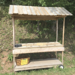 An empty farm cart, handmade from pine with a peaked roof