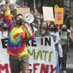 A young man with a rainbow tie dye shirt and a bullhorn leads a parade of folks on a city street