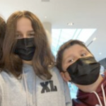 Maggie and Zack in a selfie, wearing black covid masks