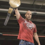JP Simms holds a gold trophy belt over his head