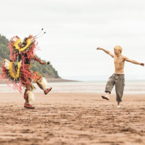 A person in Indigenous ceremonial dress and a boy dance on the red sand of a beach on the Minas Basin.