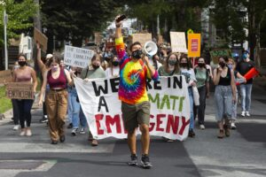 """A man wearing a tie dye shirt yells into a megaphone held in his left hand. His right arm is held up holding a phone. Behind, there are hundreds of people marching through a city street hold signs. One say, """"The climate is changing, why aren't we?"""""""