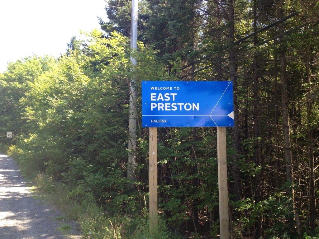 The blue welcome to East Preston sign on the side of a road in East Preston