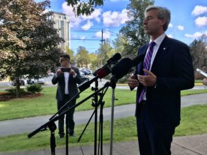 A photo of Nova Scotia Premier Tim Houston standing at a microphone during an announcement about health care in Nova Scotia.