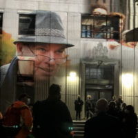 Photos of Robert Devet are projected onto the old library wall at an evening memorial. A group of people solemnly stands silhouetted in the foreground.