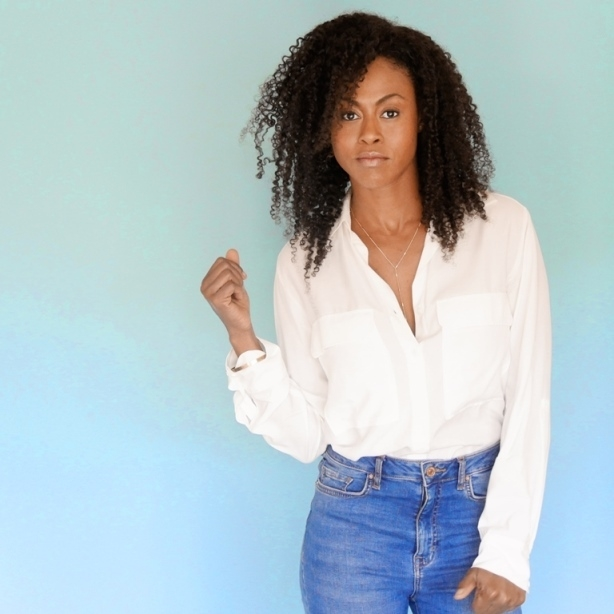 Black woman standing in front of a neutral background, wearing jeans and a white shirt