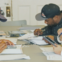 Two men and a woman work with calculators and documents at a table at the East Preston Empowerment Academy