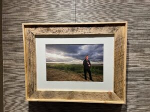 A photo of Debbie Johnson-Powell, a sign language interpreter, standing in a field. The photo is part of an exhibit of photos by Len Wagg at the Chase Gallery at the Nova Scotia Archives.