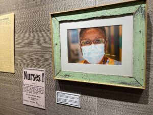 A photo from an exhibit at the Chase Gallery at the Nova Scotia Archives that shows Martha Brown, a registered nurse, wearing a blue disposable mask. Brown came out of retirement to help with the COVID pandemic response. Her photo is part of a group of photos by Len Wagg who is documenting how health care workers are helping in the COVID pandemic. This exhibition also includes newspaper clippings, photos, and other historical documents about pandemics from the Nova Scotia Archives. Those items are displayed on the walls among Len Wagg's photos.