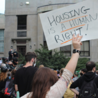 """A woman with brown hair and an off-white shirt holds up a bristol-board sign which reads """"Housing is a human right!"""" in capital letters, amongst a group of protesters at the police eviction of a homeless encampment at the former Memorial Library in Halifax, Aug. 18, 2021."""