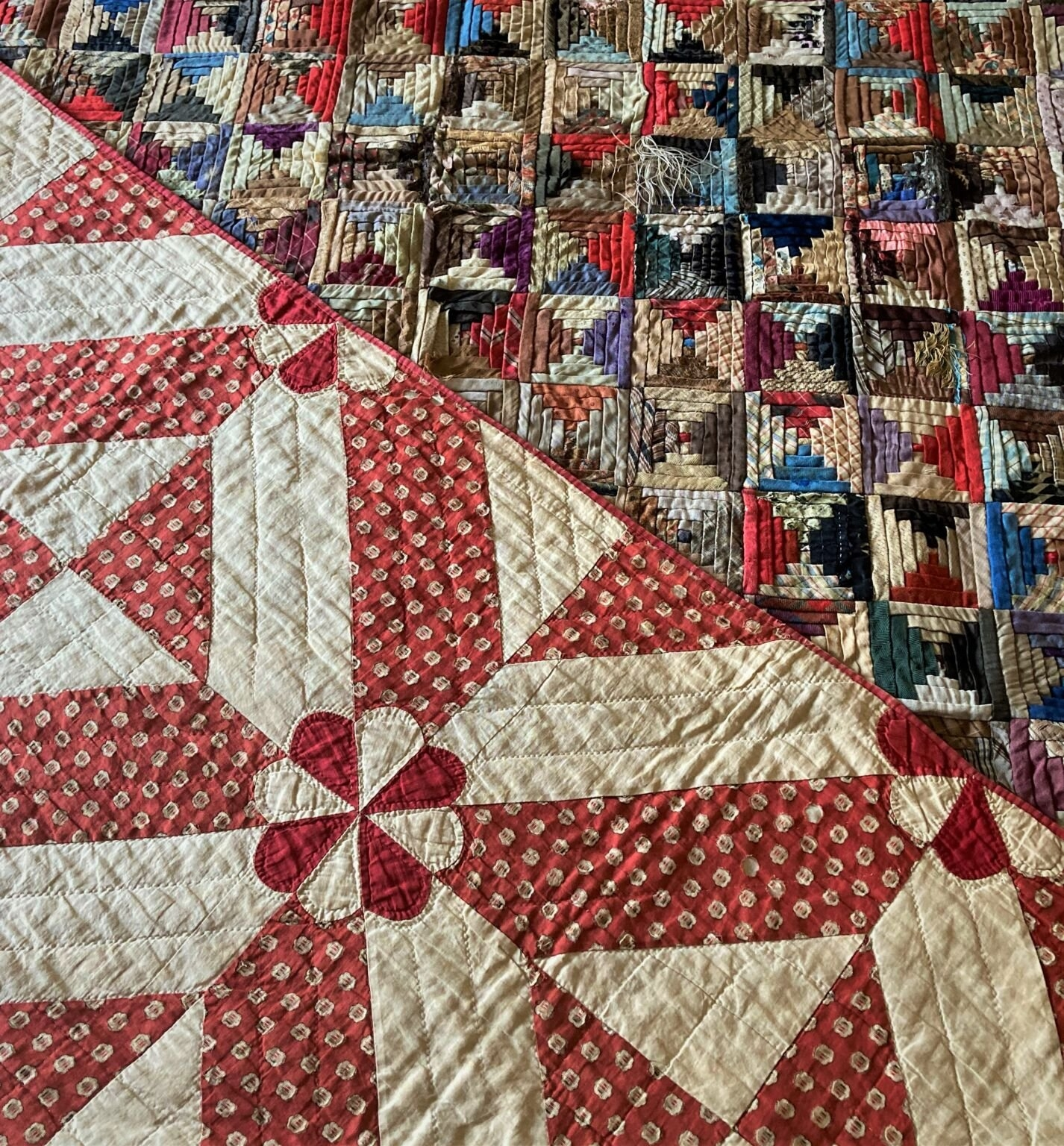 Two folded quilts, each seen in part. One is red and white, with a circle in the middle of each square of the quilt and radiating red lines on a white background. The other quilt is a riot of many different colours.