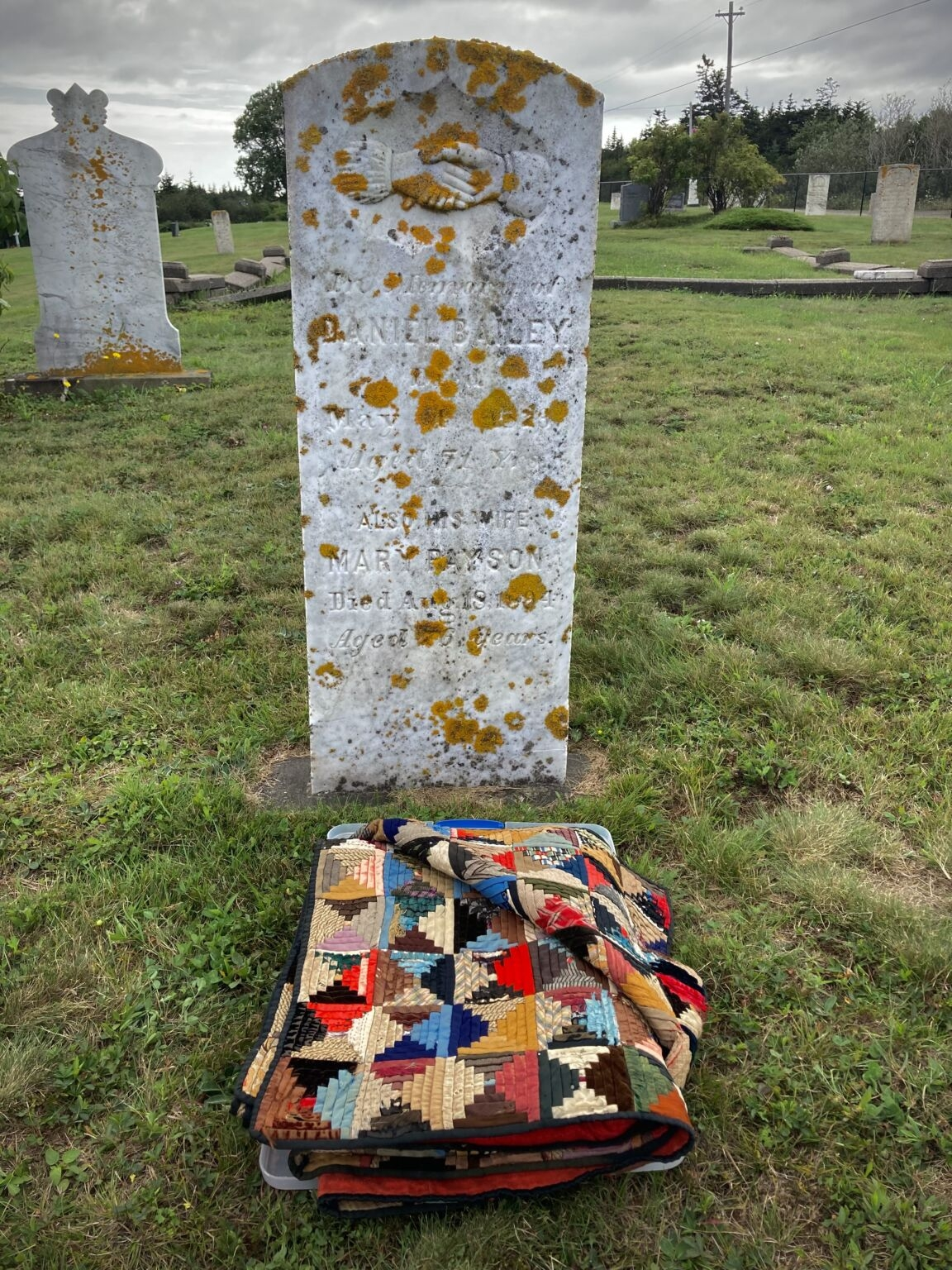 A folded quilt on the ground in front of a very old grave marker