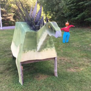 A pumpkin person stands next to a temporary statue of a stegosaurus.
