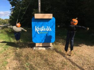 Two pumpkin people stand beside the Town of Kentville welcome sign.