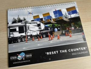 A photo of a 2022 calendar featuring photos of tall trucks getting stuck at the toll plaza at the MacKay Bridge.