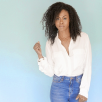 Vinessa Antoine, a Black woman with shoulder-length curly hair, standing in front of a pale blue-green background, wearing jeans and a white shirt