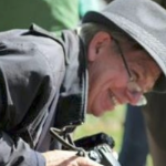 Robert Devet, looking dapper in a grey hat and coat, smiling with his camera in his hands.
