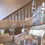 A shot of a male bartender's arms as he pulls pints
