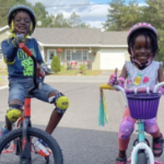 Two Black kids, aged about 6 to 8, happily pose for the camera with their bikes, wearing their bright helmets and kneepads