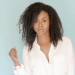 Vinessa Antoine, a young Black woman with shoulder length curly hair, against a blue green background