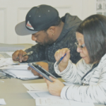 A Black man and a Black woman study with their books, papers, and a tablet at a table