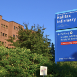 The halifax Infirmary's bright blue sign against a clear summer sky