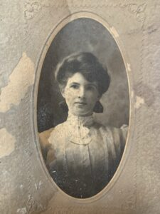 A black and white portrait of a woman from about 100 years ago. The woman is wearing a high collar white lacy blouse and has her hair in an updo. The photo was found in the walls in a house in Halifax's Hydrostone area. The homeowners are looking to identify the woman in the photo.