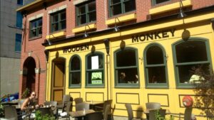 A photo of the exterior of The Wooden Monkey, a restaurant on Grafton Street in downtown Halifax. The front of the restaurant is brick with yellow paint. Customers are on the patio and inside.