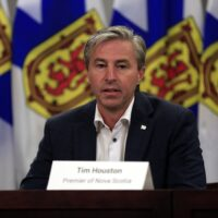A man wearing a dark suit, white shirt and no tie speaks at a podium. In the background are four Nova Scotia flags, coloured blue, yellow and red.